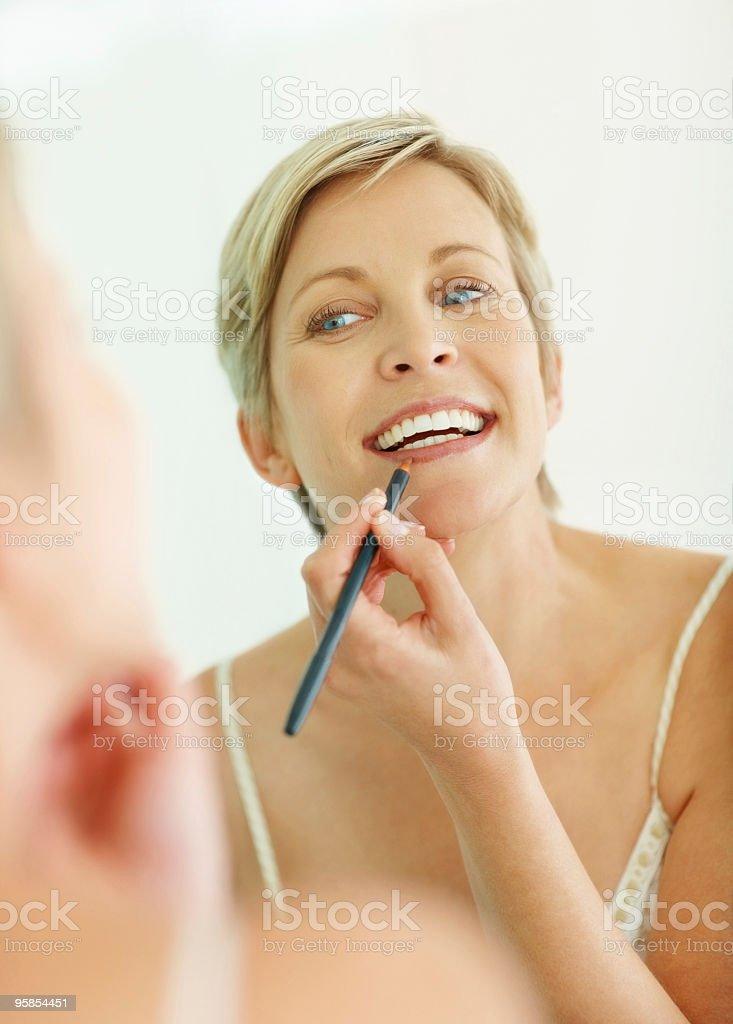 Mid adult woman applying make up stock photo