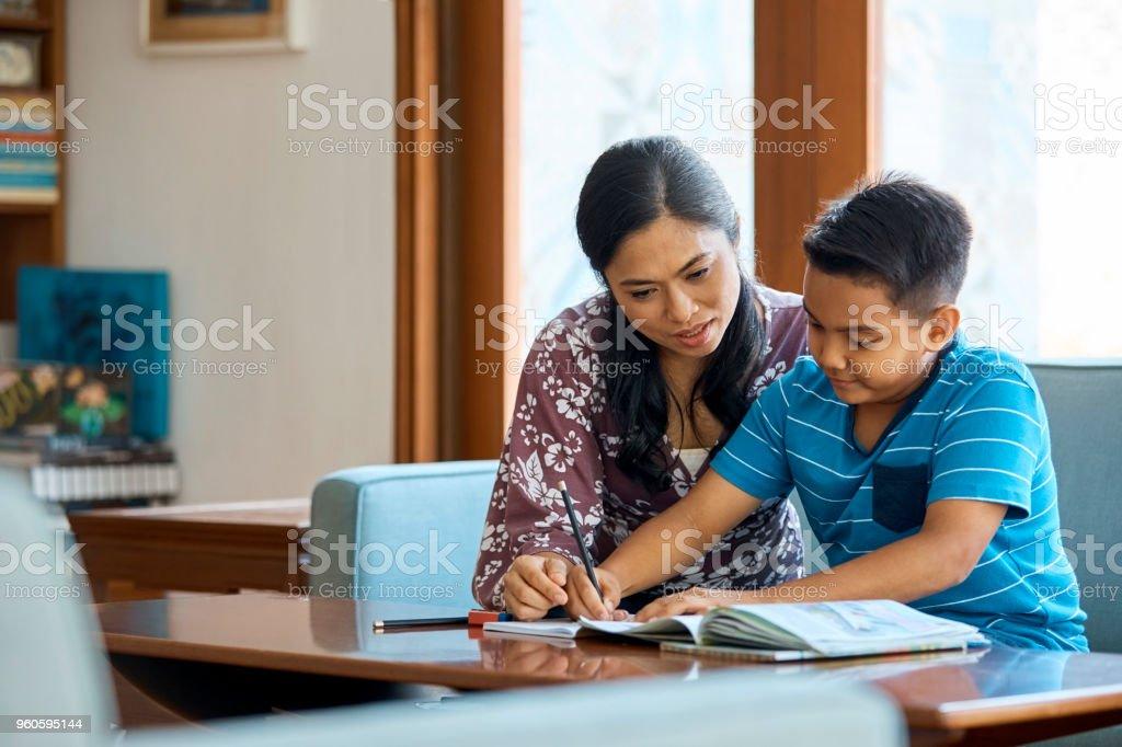 Mitte Erwachsene Frau Sohn im Studium zu Hause unterstützen – Foto