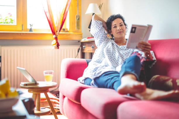 mid volwassen vrouw thuis - woman home magazine stockfoto's en -beelden