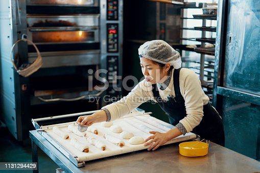 Mid adult woman baking bread in an industrial kitchen in Japan