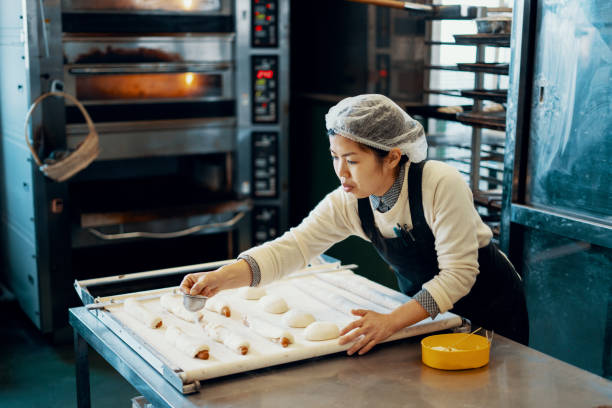 mid adult woman baking bread in an industrial kitchen - panettiere foto e immagini stock