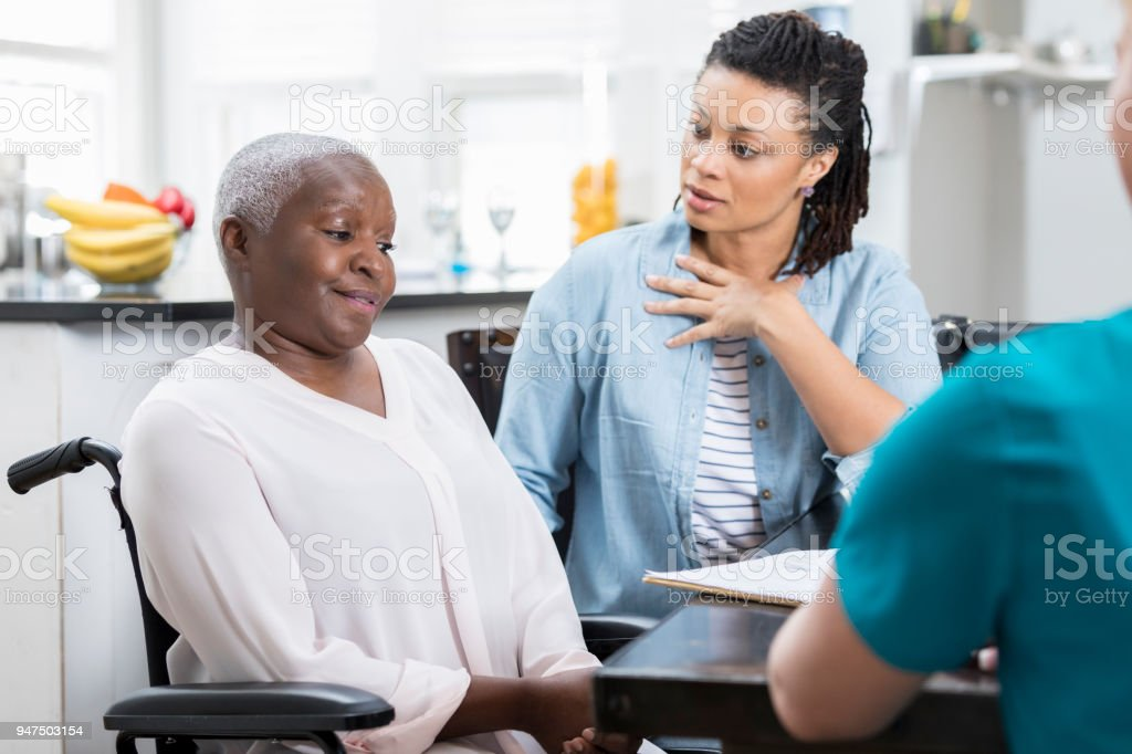 Mid adult woman discusses her mother's health with nurse stock photo