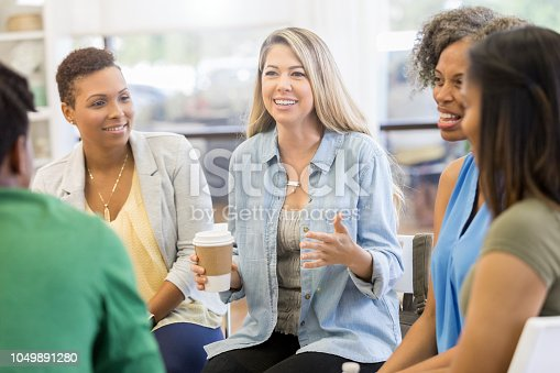 1055095320 istock photo Mid adult woman discusses something during support group 1049891280