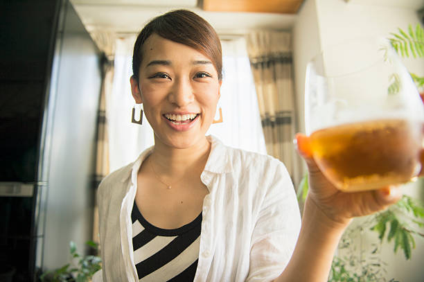 mid adult woman drinking beer at home - 僅一名中年女子 個照片及圖片檔