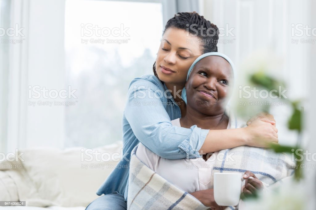 Mid adult woman embraces her senior mom stock photo