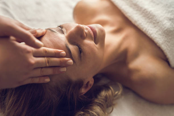 Mid adult woman enjoying in her relaxing head massage at the spa. stock photo