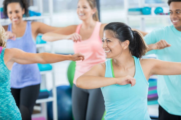 mid adult woman enjoys aerobics class - dance class stock photos and pictures