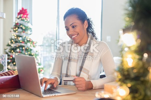 A smiling mid adult woman sits at a table in her home and types on a laptop computer.  She holds a credit card in one hand as she Christmas shops online.