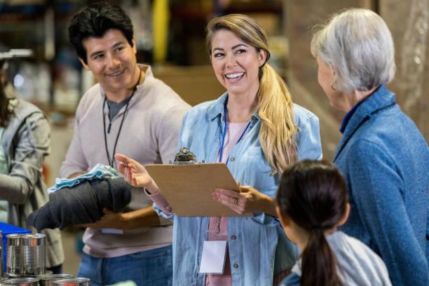 mid adult woman enjoys leading food bank volunteers - organizzazione no profit foto e immagini stock
