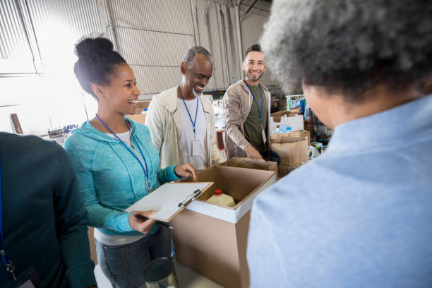 mid adult woman enjoys organizing food bank donations - volunteer stock photos and pictures