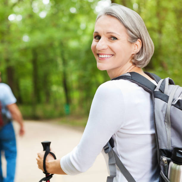Mid adult woman enjoys outdoor hiking trail stock photo