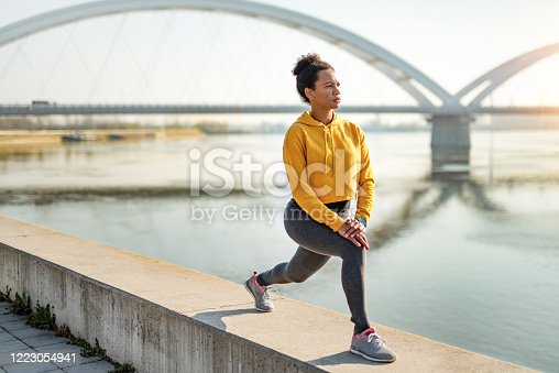 African American woman working out next to the river.