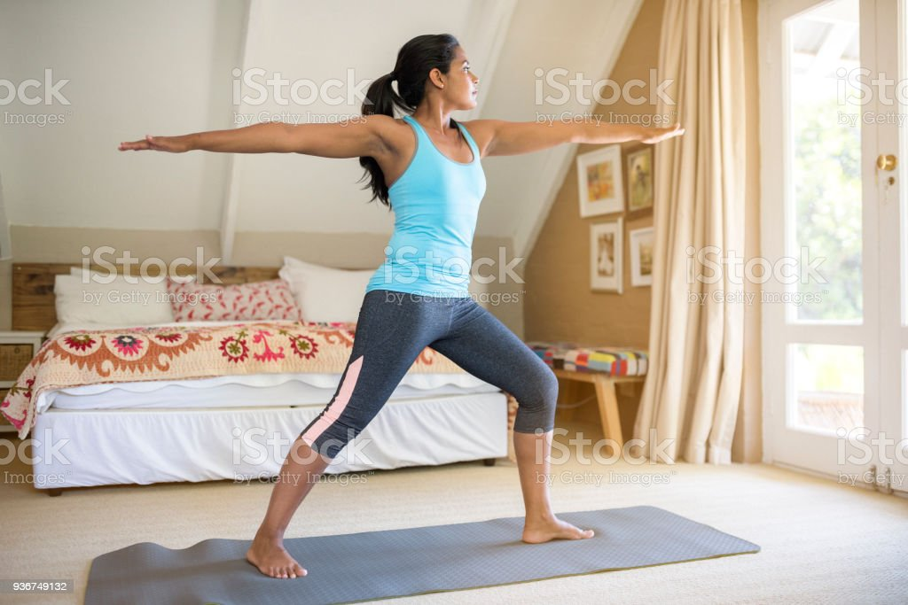 Mid adult woman exercising yoga in bedroom at home stock photo