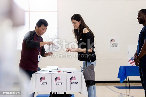 The mid adult woman gets help from the mature adult volunteer to sign up to vote in the election.  The mid adult man in line beind her holds an American flag
