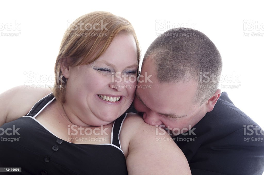 Mid adult woman giggling as fiance nuzzles shoulder. royalty-free stock photo