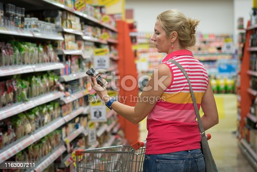 Mid adult woman Groceries Shopping in supermarket