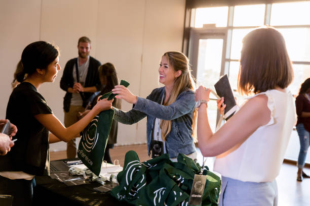 Mid adult woman hands out conference tote bags A mid adult woman smiles as she hands out conference tote bags. college fair stock pictures, royalty-free photos & images