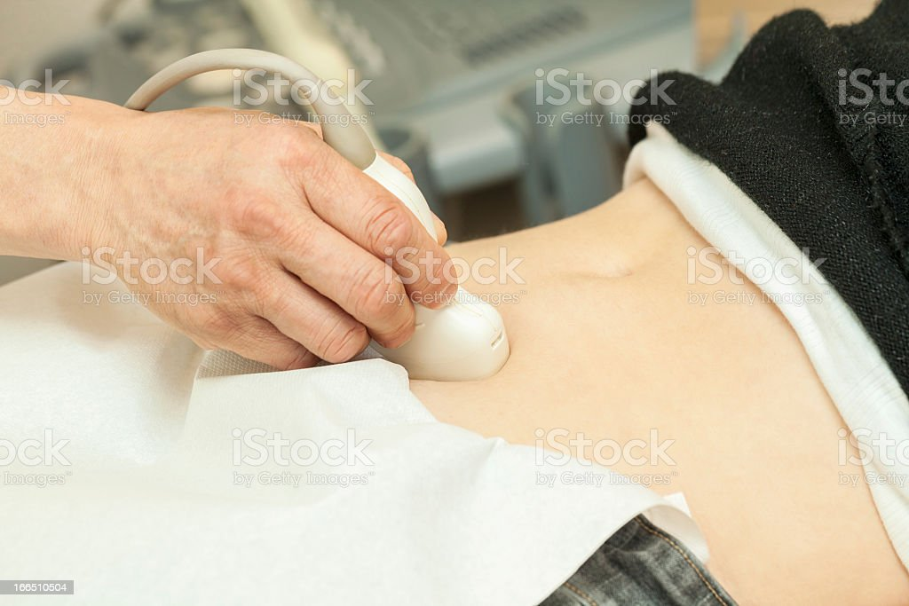 Mid adult woman having abdominal ultrasound stock photo