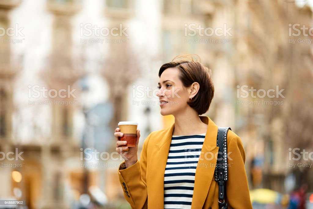 Mid adult woman holding disposable cup in city stock photo