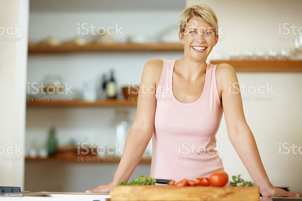 Mid adult woman in kitchen with vegetables royalty-free stock photo
