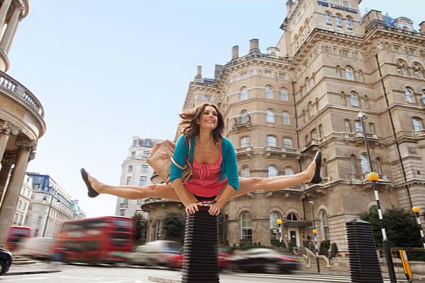 adulto de mediana edad mujer en vestido rosa leapfrogging a city street - piernas abiertas mujer fotografías e imágenes de stock