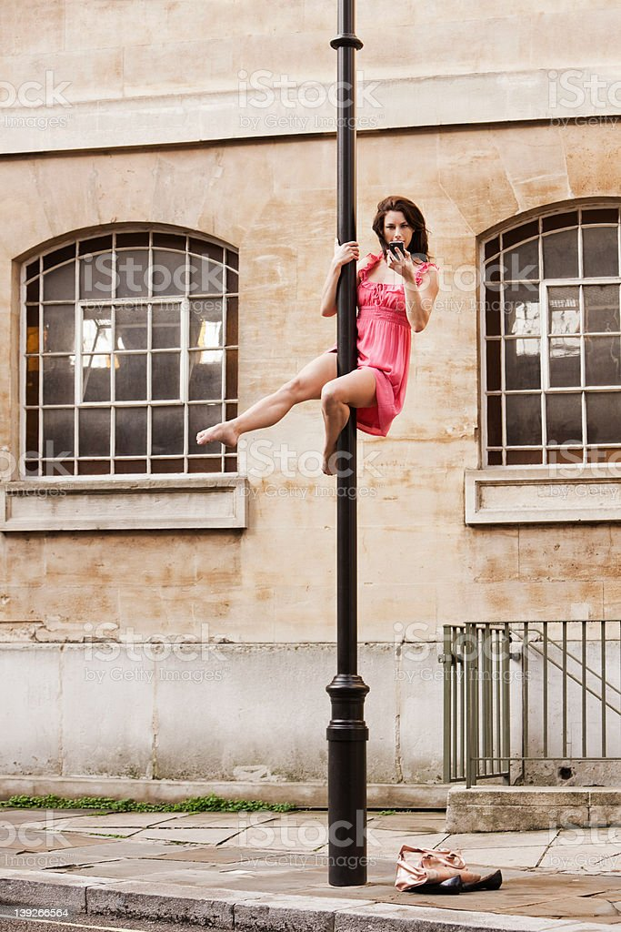 Mid adult woman in pink dress using cellphone on street lamp in city stock photo