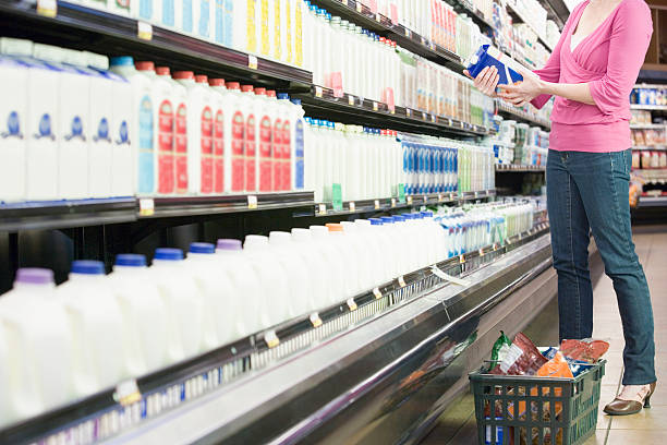 Mid adult woman in supermarket holding milk Mid adult woman in supermarket holding milk gallon stock pictures, royalty-free photos & images