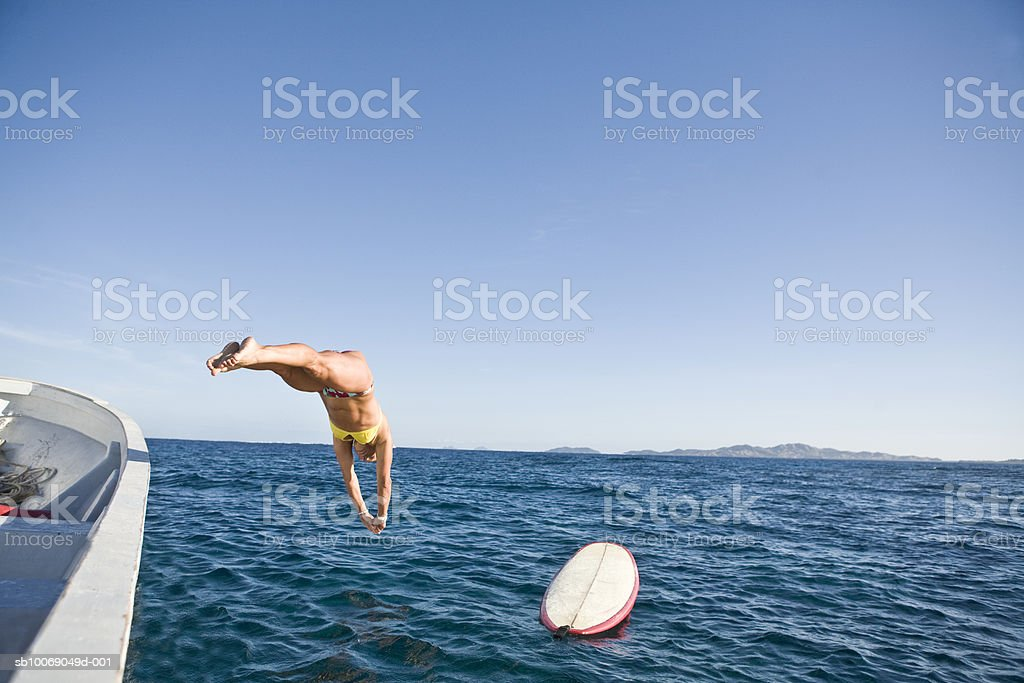Mid adult woman jumping from boat into sea foto de stock royalty-free