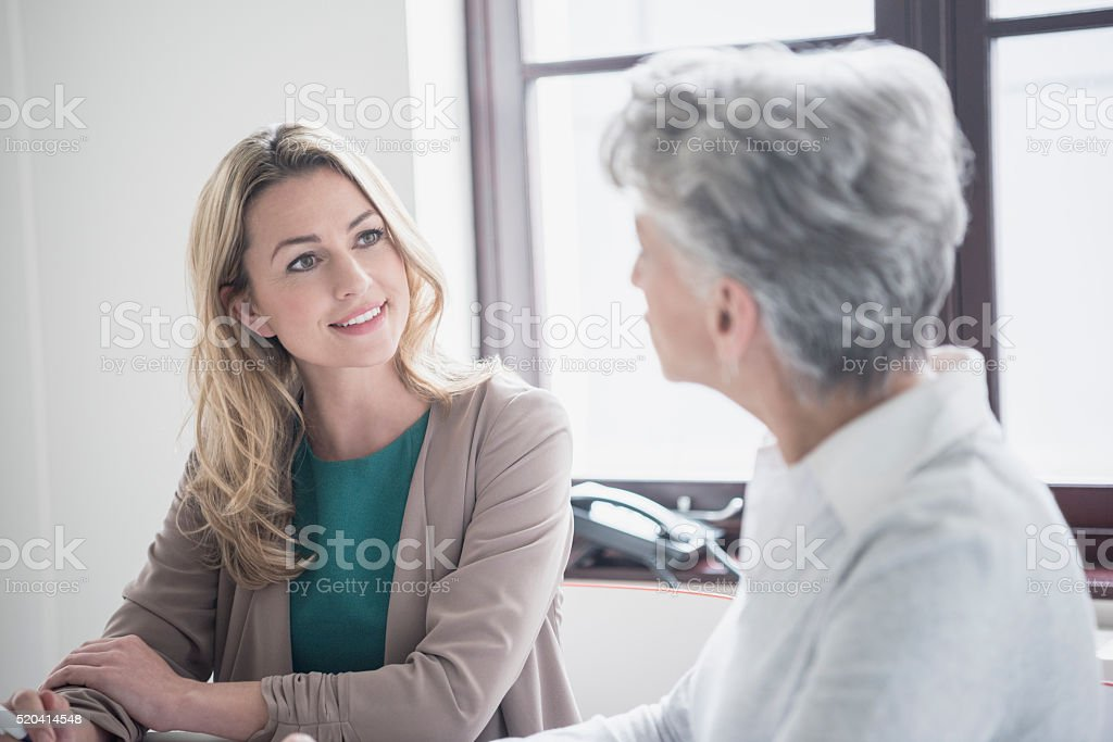 Mid adult woman listening to mature female colleague in meeting stock photo