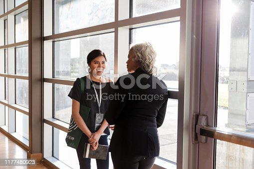 During a quiet moment in the weekend conference, a mid adult woman listens eagerly to advice given by the mature adult speaker.