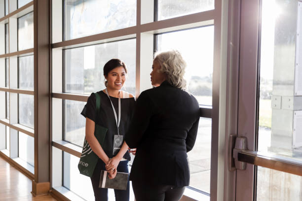 Mid adult woman listens eagerly to mature conference speaker During a quiet moment in the weekend conference, a mid adult woman listens eagerly to advice given by the mature adult speaker. college fair stock pictures, royalty-free photos & images