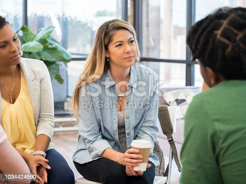 istock Mid adult woman listens intently to fellow group counseling paticipant 1034424590