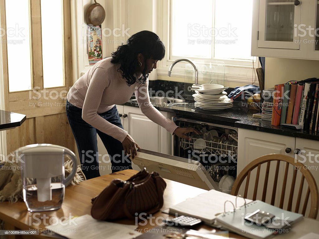 Mid adult woman loading dishwasher royalty-free stock photo