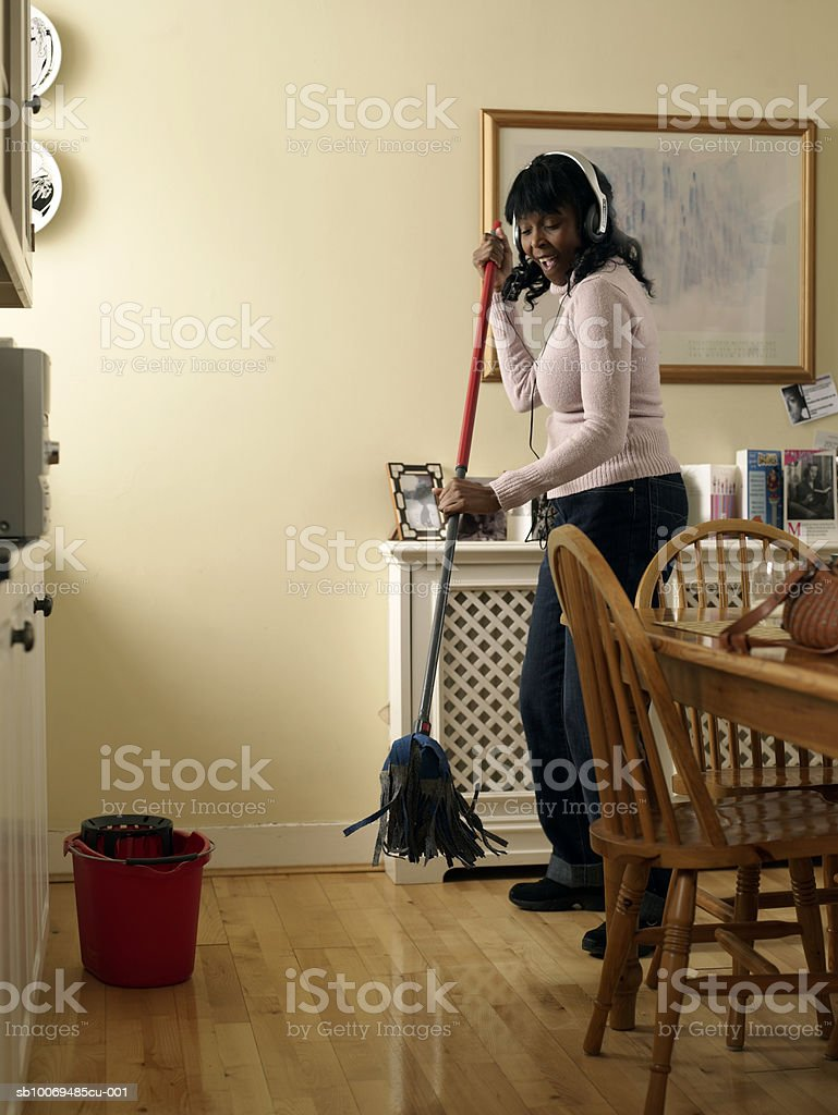 Mid adult woman mopping kitchen floor wearing headphones royalty-free stock photo