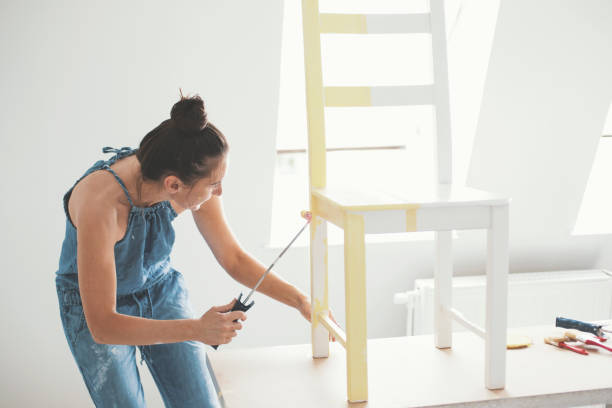 Mid adult woman painting chair stock photo