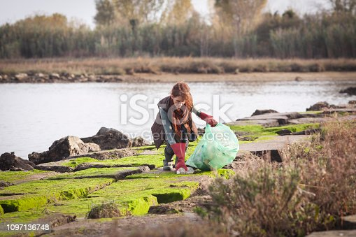 Mid Adult Woman Picking Up Garbage on Riverbank.