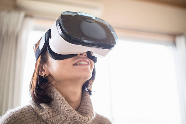 Mid adult woman playing in virtual reality glasses in bedroom ストックフォト