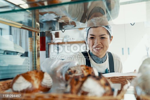 istock Mid adult woman putting bread on display in her small business bakery 1131294457