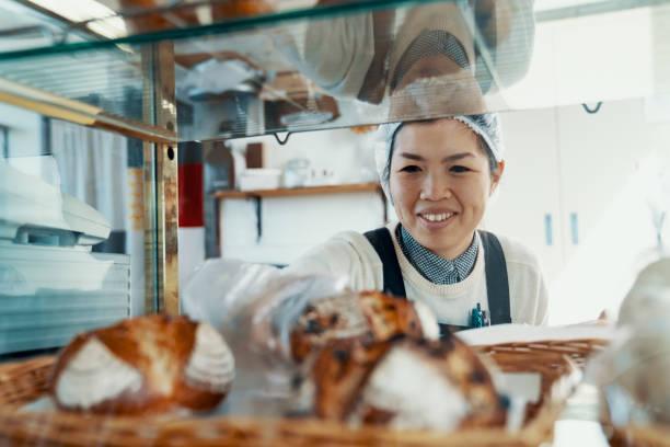 mid femme adulte mettant le pain sur l'affichage dans sa boulangerie de petite entreprise - boulanger photos et images de collection