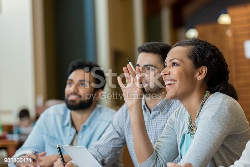 Confident mid adult college student raises her hand to ask or answer question while attending a college class.
