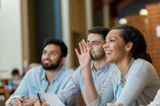 Mid adult woman raises hand duirng college class stock photo