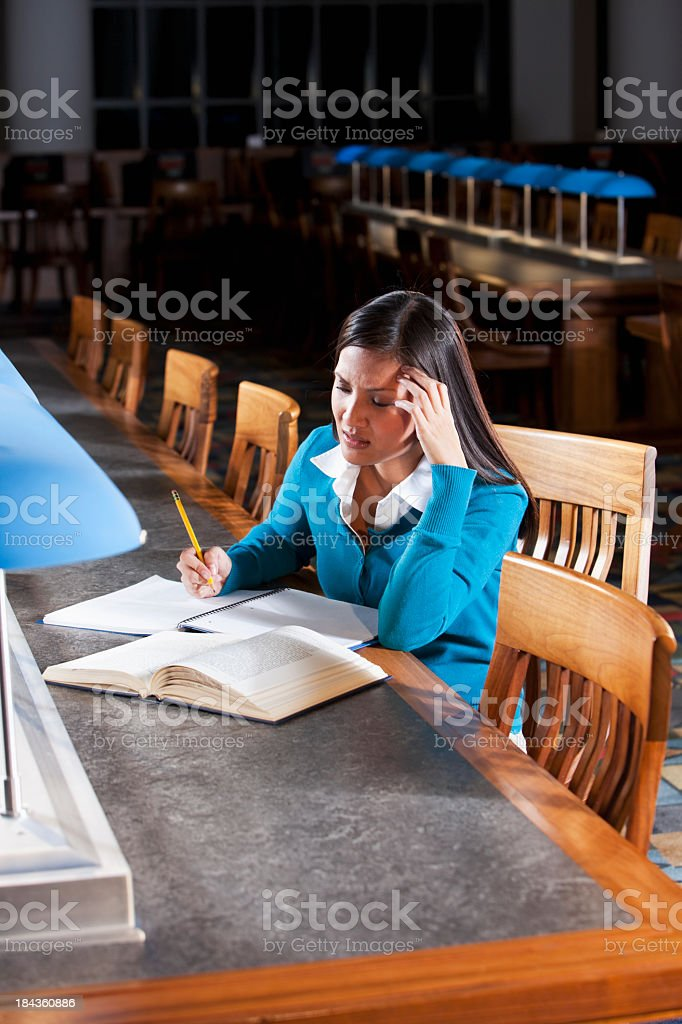 Mid adult woman reading in library, university student stock photo