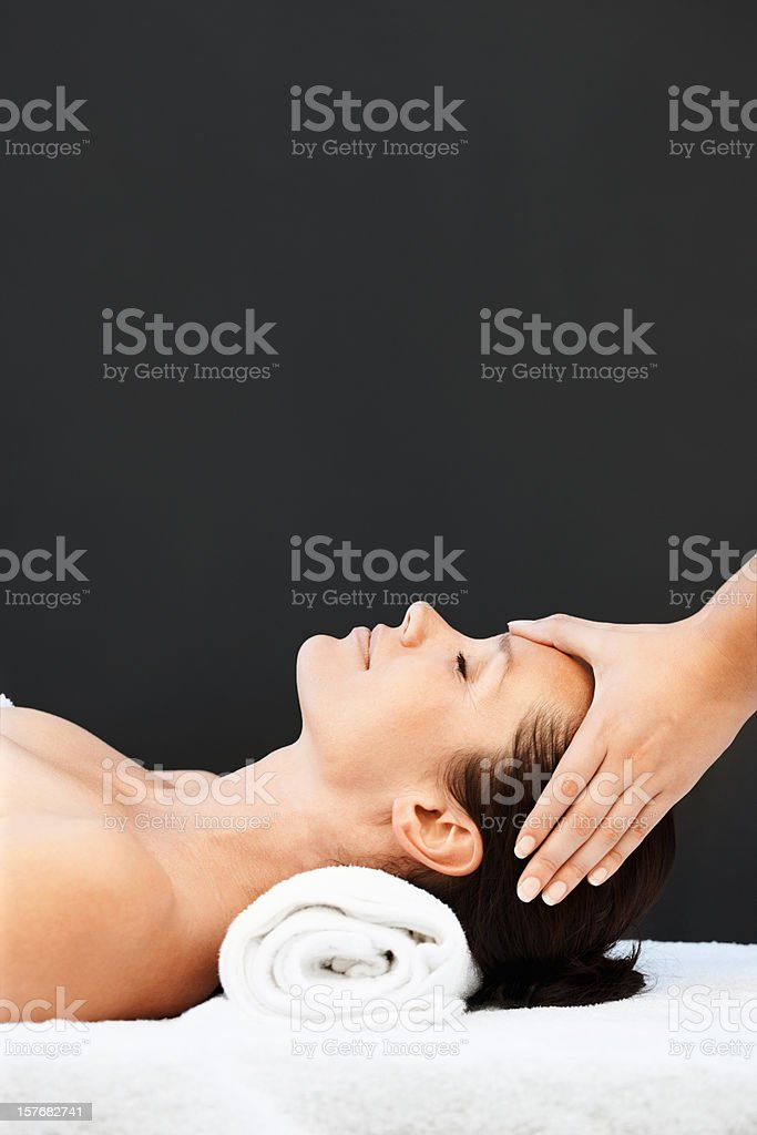 Mid adult woman receiving head massage on black background stock photo