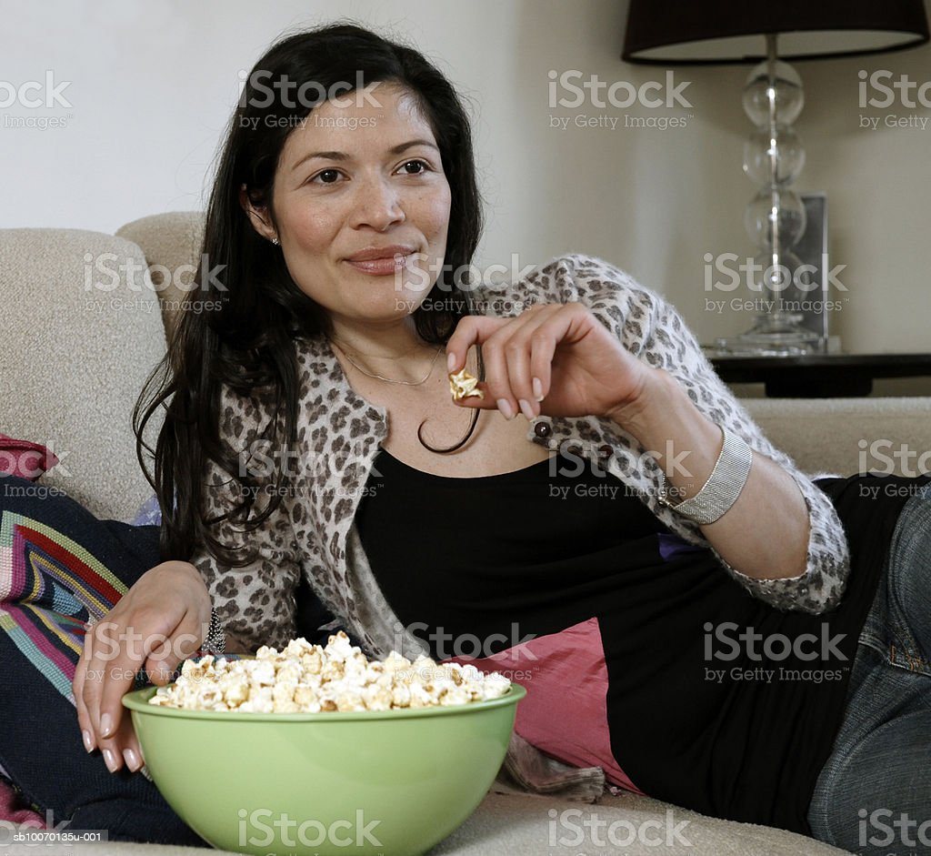 Mid adult woman reclining on sofa and eating popcorn 免版稅 stock photo