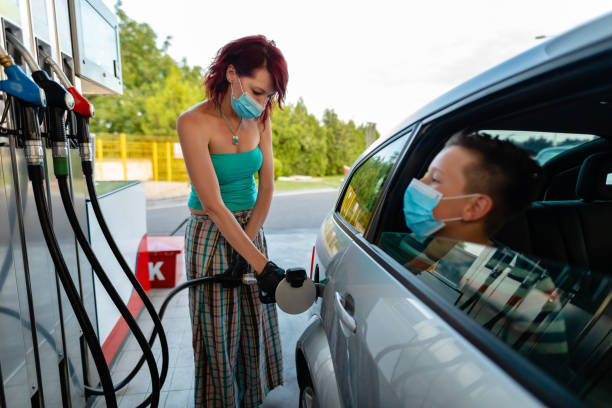 Mid adult woman refueling her car at the gas station while her son waiting for her at the back seat stock photo
