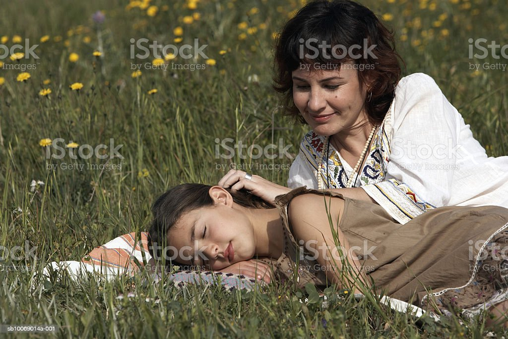 Mid adult woman relaxing with daughter (8-9) in meadow royalty free stockfoto