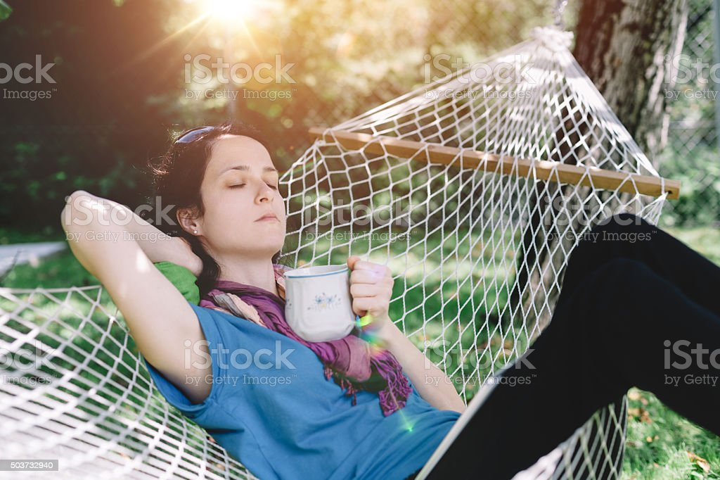 Mid adult woman resting at the backyard stock photo