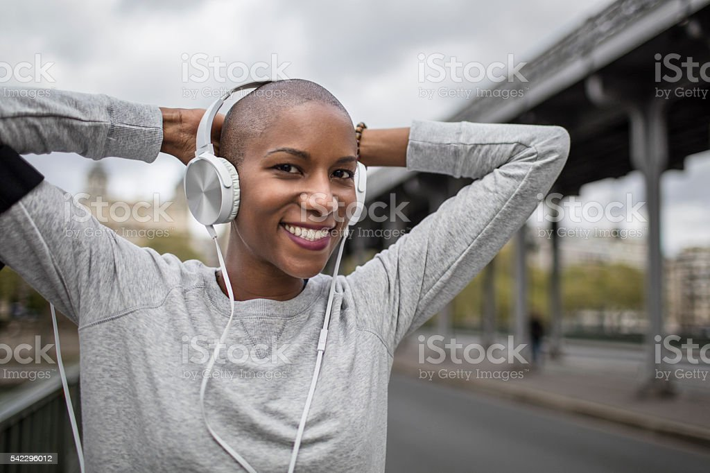 Mid adult woman runner listening to music doing sport stock photo