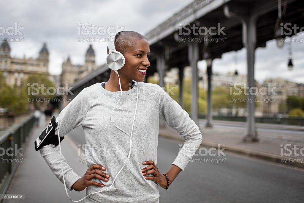 Mid adult woman runner listrening to headphones in Paris stock photo
