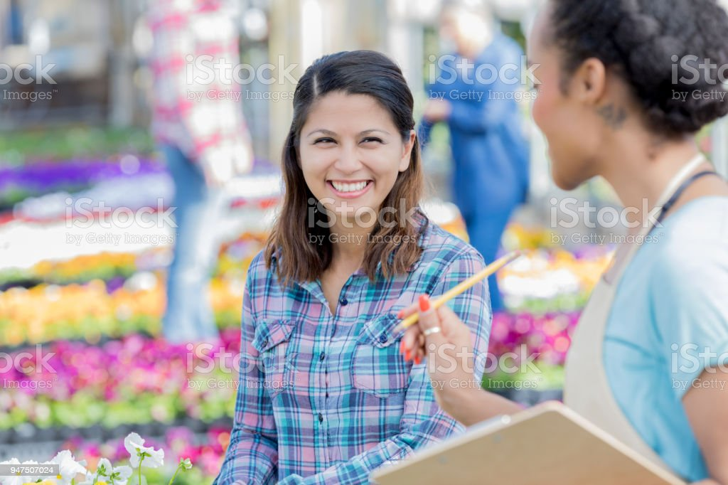 Mid adult woman shops in plant nursery stock photo